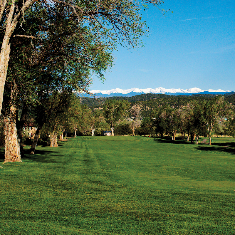 picture of golf course fairway with rocky mountians in the background