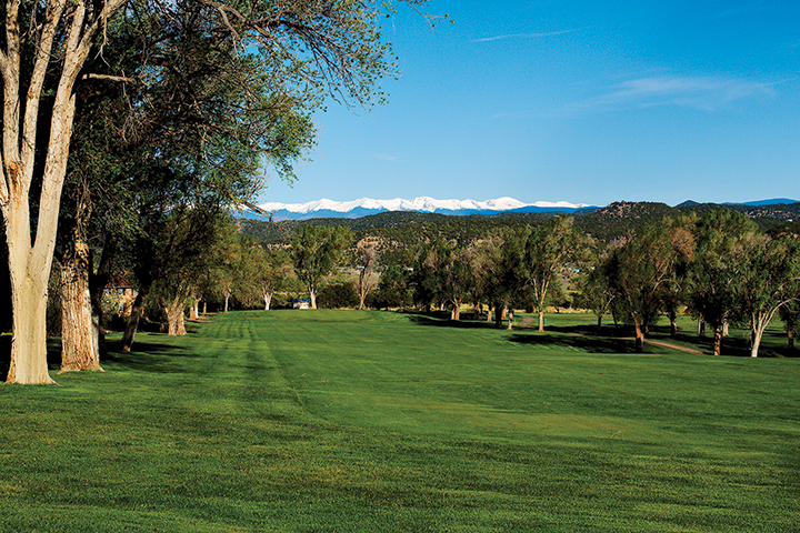 view looking down a green fairway toward the pin with mountains in background