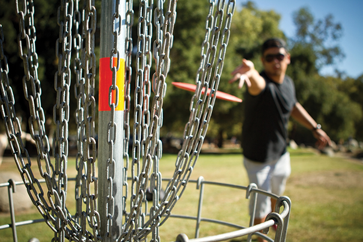 disc golf player tossing disc into basket