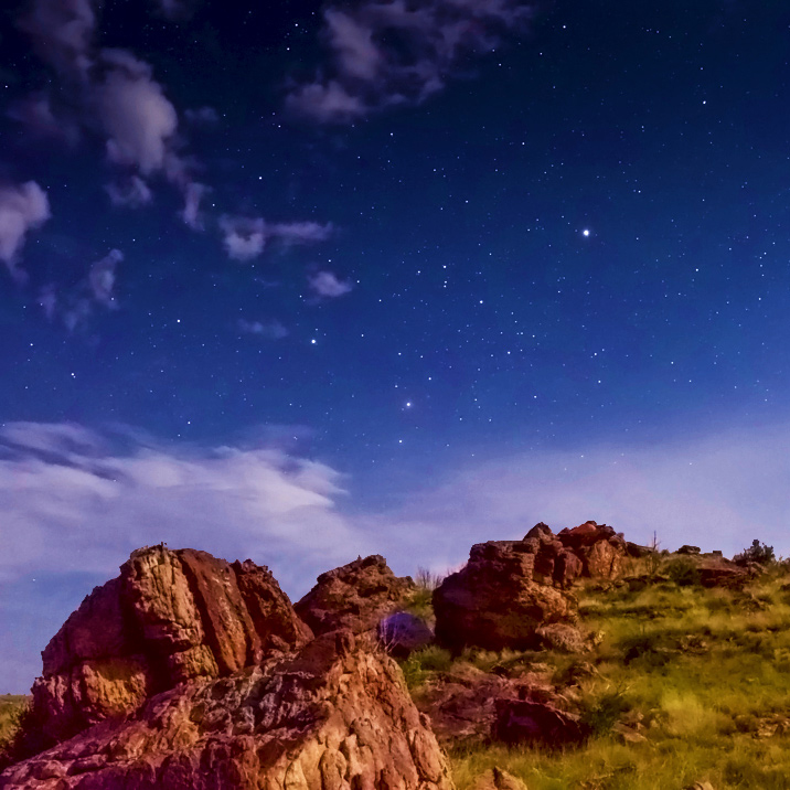 Photo contest winner depicting starry evening and red rock outcroppings on a mountain side.
