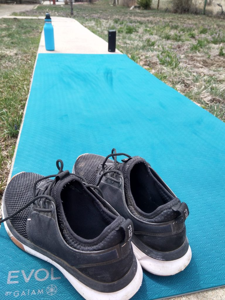 Photo of a yoga mat, water bottle, and running shoes outside