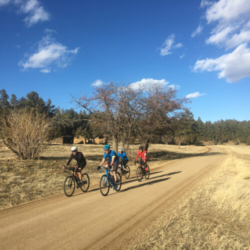 Image of four cyclists riding on gravel